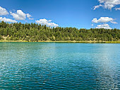 blue lake and green forest on a sunny summer day