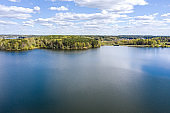 panoramic landscape of forest lake shore in summer sunny day