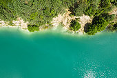 aerial view of summer forest and quarry lake with green water. view from above