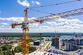 modern apartment buildings complex under construction. yellow building cranes on construction site against blue sky background. aerial photography