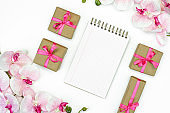 flat-lay of Gift present boxes with  pink ribbon and orchid flowers on white background top view.  Note book or diary writing. Gift or present spring concept. Copy space