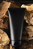 Black unbranded tube with moisturizing facial cream. Flacon on stones background. Mockup style, vertical picture. Professional skincare and beauty. Mans cosmetics and wellness concept