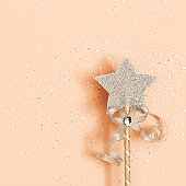 Glowing, glittering star on pink background. Minimal  greeting card for New Year or Christmas holidays. Magic star, fulfillment of wishes, dreams.  Top view, pastel color.