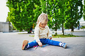 Adorable toddler girl drawing with colorful chalks