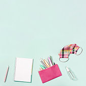 Flat lay with notebook and stationery for girl, pink fabric mask for protection from infections and hand sanitizer.
