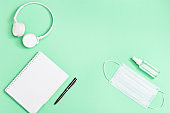 Flat lay with stationery for school, education and personal protective equipments. Face medical mask, hand sanitizer, notebook, pen,  white headphones. Top view and copy space.
