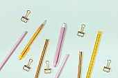 Flat lay with stationery for school or office. Pink and golden colored pencils, pens and metal paperclips.