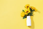 Autumn flower of sunflower in white vase on yellow background. Natural bright yellow blossom with green leaves.