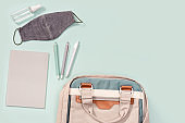 Backpack with school supplies, face mask and hand sanitizer, schoolboy badge, copybooks, pens