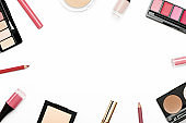 Cosmetics from above border on white background. Blusher, face powder container, eyebrow shadow, nail polish, lip gloss and pencil. Decorative make up frame top view. Female glamour beauty products