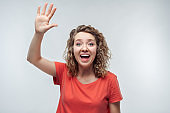 Portrait of friendly blonde girl waving hand and looking at camera. Studio shot, white background.Human emotions concept