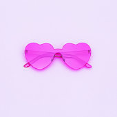 Minimal style fashion photography with heart shaped glasses on purple background with copy space. Pink modern sunglasses and reflection of palm leaf. Trendly summer concept.