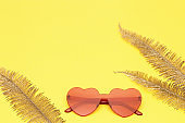 Minimal style fashion photography with heart shaped glasses and golden palm leaves on yellow paper background. Modern red sunglasses. Trendly summer concept. Copy space.