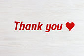 "Text ""thank you"" and red colored heart on white wooden background with copy space. Words of gratitude and expressions of love. View from above."