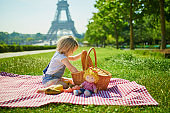 Cheerful toddler girl having picnic near the Eiffel tower in Paris
