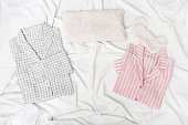 Pink and grey pajamas for men and women, and sleep mask for eye on white cotton bedsheet. Comfortable homewear for sleeping. Top view. Flat lay.