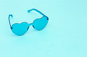 Minimal style fashion photography with heart shaped glasses on blue background. Light blue modern sunglasses. Trendly summer concept. Copy space.