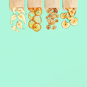 Healthy snack, set of dried fruits. Dehydrated fruit chips of apple, banana, persimmon, pear in paper package. Diet food. Top view.