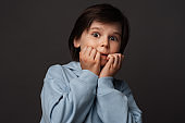 Image of scared boy covering his mouth with hands. Fright, phobia and facial expression concept