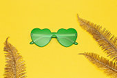Minimal style fashion photography with heart shaped glasses and golden palm leaves on yellow paper background. Modern green sunglasses. Trendly summer concept. Copy space.