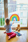 Adorable toddler girl painting rainbow on the window glass