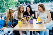 Female friends in cafe looking at mobile phone
