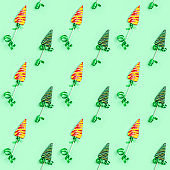 Color candy creative seamless pattern for New Year or Christmas. Lollipops shaped like Christmas tree on green background. Happy Holidays and celebrations sweets.