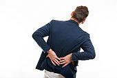 Back view of man wearing smart casual clothes gesturing pain