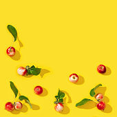 Pattern from small red apples and green leaves with dark shadows