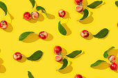 Seamless creative pattern from ripe small red apples and green leaves on yellow color background.  Food concept. Vegetable background.