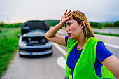Worried woman with damaged car