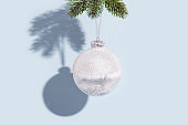 New years ball, glass transparent white colored holiday toy on blue background. Christmas greeting card.
