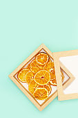 Healthy snack. Homemade dehydrated fruit chips of tangerine on blue background. Dry tangerine in paper package. Diet food. Top view and copy space.