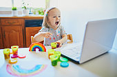 Toddler girl playing modelling clay in front of laptop