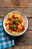 Spanish fried potatoes with willow also called potatoes bravas on wooden background