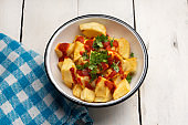 Spanish fried potatoes with willow also called potatoes bravas on white background