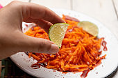 Mexican grated carrot with chamoy sauce and chili powder on white background