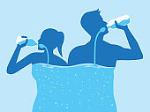 Man and women with water in his body lifting a water bottle and drinking water from bottle flow into body.