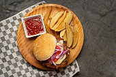 Tuna burger with potato fries on dark background