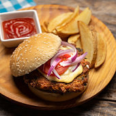 Tuna burger with potato fries on wooden background