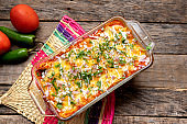 Mexican red baked enchiladas with melted cheese and sour cream on wooden background