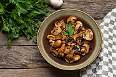 """Mexican mushrooms with garlic and guajillo chili peppers also called """"al ajillo"""" on wooden background"""