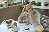 Mature adult man working at home in the mask ( emotional stress )