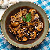 """Mexican mushrooms with garlic and guajillo chili peppers also called """"al ajillo"""" on white background"""