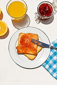 Bread toast with orange juice and jam on white background