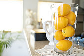 Lemons in the glass vase on the kitchen counter