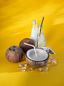 Coconut milk and coco water at yellow background.