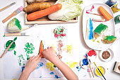 Top view close up of toddler boy child hands, kid making artwork from vegetable stamping at home, Fun art and crafts for toddlers