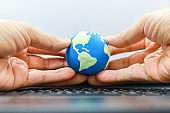 Global Communication Technology Concept. Man hand holding mini world ball with keyboard computer.