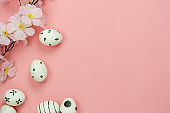 Top view shot of arrangement decoration Happy Easter holiday background concept.Flat lay colorful bunny eggs with flower accessory ornament on modern pink paper at office desk.Design pastel tone.